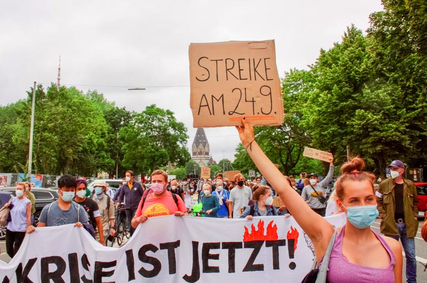"""Eine fff-Demonstrantin mit Schild """"Streike am 24.9."""""""
