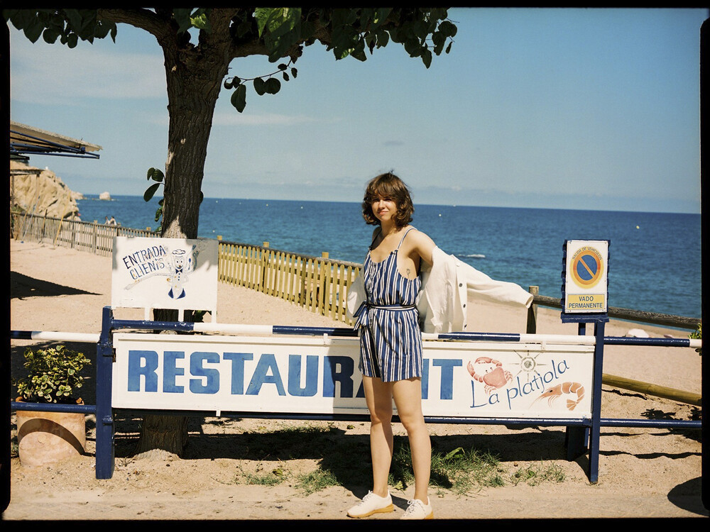 Eine Frau steht in einemöko-fairen Outfit am Meer
