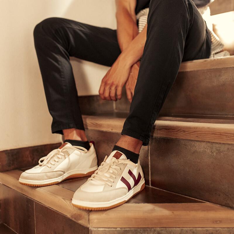 EIn Mann mit Sneakern sitzt auf einer Treppe