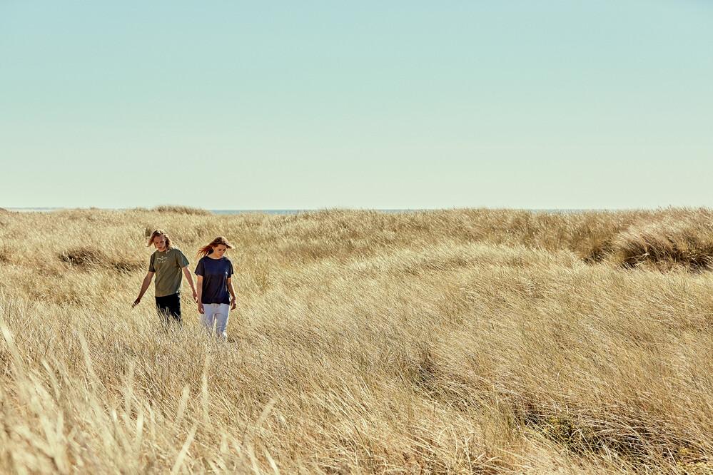 Zwei Personen laufen über eine grasbewachsene Düne
