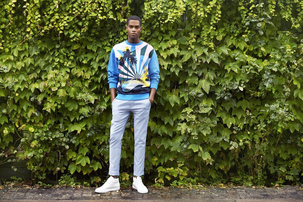 Ein junger Mann in einem lässigen, nachhaltigen Outfit